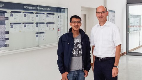 2 men in front of an information board.