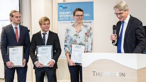 Presentation of the VWI Graduation Award. 3 persons holding a certificate in their hands. The person on the right side speaks and holds a microphone in his hand.