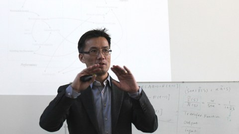 A man with glasses gives a presentation.