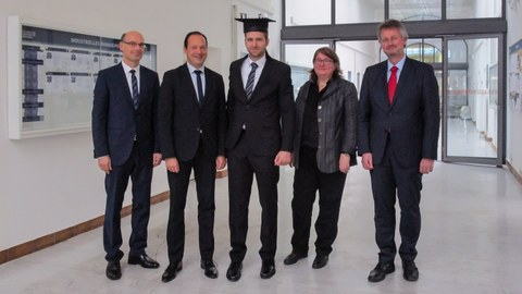 5 people wearing suits. The man in the middle is wearing a doctor's hat.