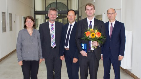 5 persons in suits. The 2nd man from the right holds a bouquet of flowers in his hand