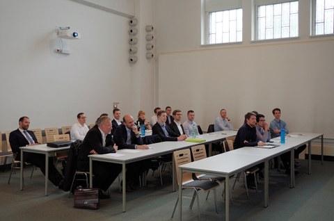 Mehrere Personen sitzen an Tischen in 3 Reihen und hören einem Vortrag zu.