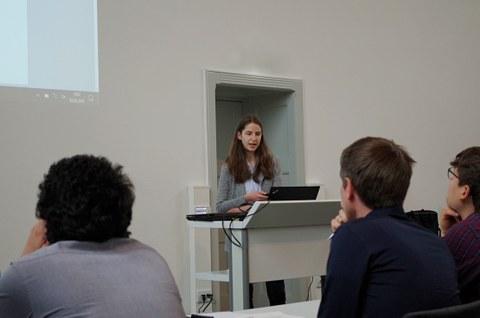 Eine Lehrstuhlmitarbeiterin hält einen Vortrag vor mehreren Personen.