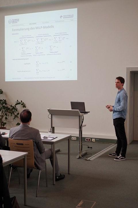 Ein Lehrstuhlmitarbeiter hält einen Vortrag.