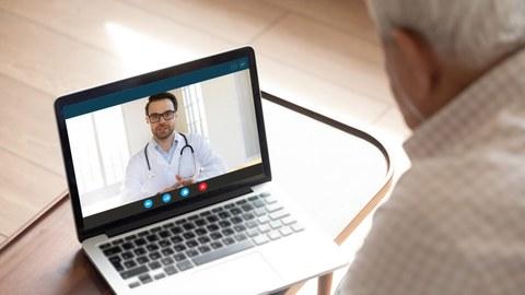 Ein älterer Patient sieht vor einem Laptop und hört einem Arzt zu.