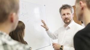 Das Foto zeigt eine Tafel, an der Formel und Grafiken geschrieben stehen. Vor der Tafel steht der Dozent, der drei Studierenden etwas erklärt.