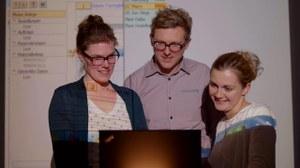 Das Foto zeigt drei Seminarteilnehmer, die im Beamerlicht stehen.