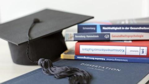 Man sieht eine Dissertation, einen Stapel Bücher und einen Doktorhut