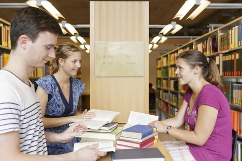 You see three students sitting in the library and talking to each other.