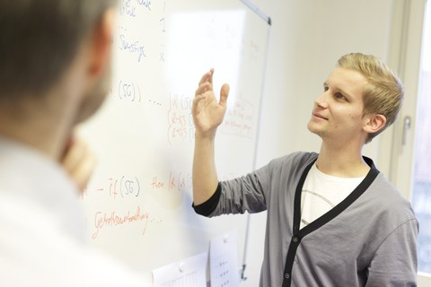 You see a student standing in front of a flipchart who is explaining something to another person.