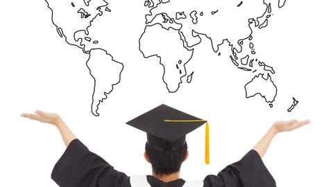Picture of a graduate photographed from behind with a bachelor hat in front of the graphic of a world map, arms up