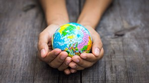 Photo of two children's hands holding a small globe.