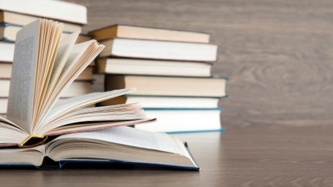 Photo of an opened book with books in the background