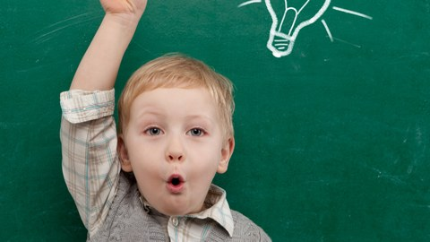 Child with a raises hand in front of a blackboard on which a light bulb is drawn