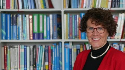 Foto von Fr. Prof. Narciss vor einem Bücherregal