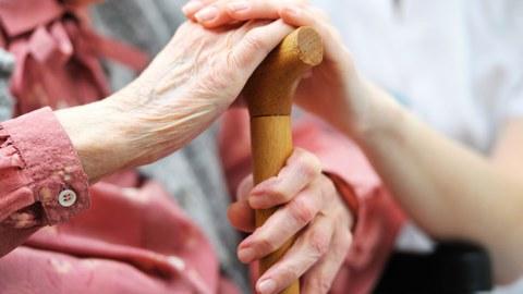Hände ältere Dame mit Stock