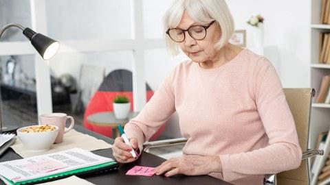 Ältere Frau sitzt am Schreibtisch