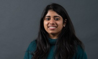 The picture shows a woman with long brown hair who is Neha Goveas