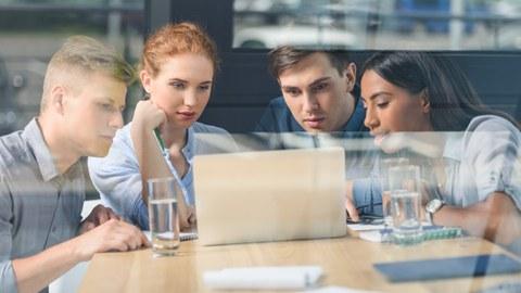 Das Foto zeigt vier junge Personen hinter einer Glasfront, die gemeinsam an einem Tisch sitzen und konzentriert in einen Laptop schauen.