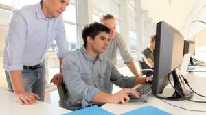 Das Foto zeigt zwei Studierende vor einem Computer. Der Junge sitzt auf dem Stuhl und tippt auf der Tastatur. Der Dozent steht daneben und schaut ebenfalls auf den Bildschirm.