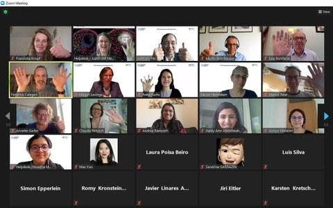 Ein Bildschirmfoto aus der Zoom-Sitzung. Es sind kleine Kacheln mit Bildern der Teilnehmer zu sehen. Einige Teilnehmer winken mit den Händen, einige geben Daumen nach oben.