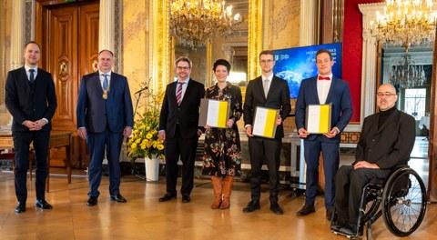 sechs Personen in Anzügen posieren zu einem Foto in einem goldenen Raum