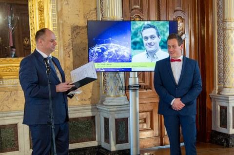 Zwei Männer in Anzügen stehen vor dem TV-Bildschirm in einem goldenen Raum