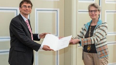 Ein Mann auf der linken Seite erhält ein Diplom von der Frau auf der rechten Seite. Beide lächeln