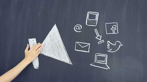 Megaphon mit Smybolen von Social Media Kanälen an Tafel gezeichnet