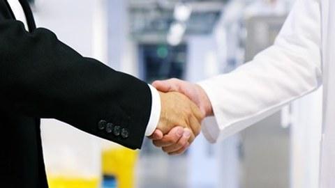 Mann im Anzug und Mann im Kittel schütteln sich die Hände
