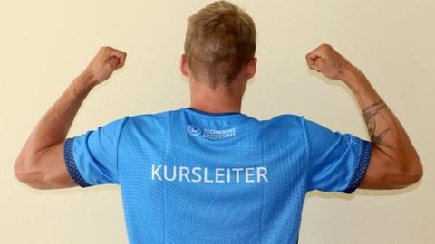 """Foto: muskulöser Mann mit blauem T-Shirt, auf dem """"Kursleiter"""" steht"""