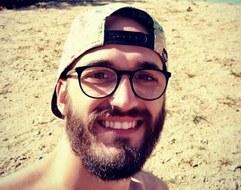 Foto: lächelnder Mann mit Bart, Brille und Basecap