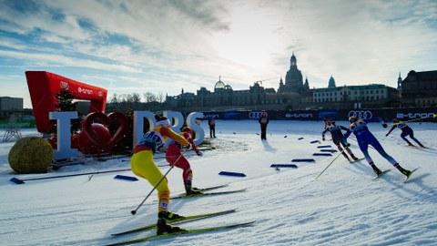 Foto: Langläuferinnen im Rennen vor der Silhouette der Frauenkirche