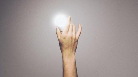 Foto: eine Hand hält eine leuchtende Glühbirne
