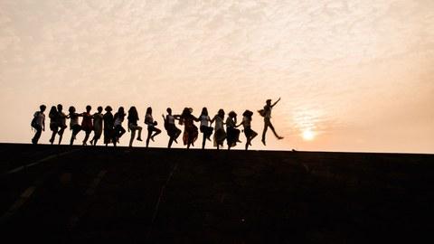 Foto: Tanzende Menschenkette vor Sonnenuntergang