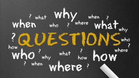 """Grafik: schwarze Tafel mit dem Wort """"Questions"""" in gelb und vielen Fragezeichen in weiß rundherum"""