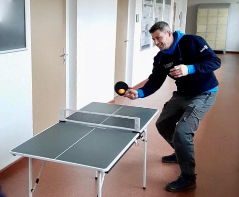 Foto: Mann in blauem Kapuzenpullover spielt an einer Mini-Tischtennisplatte Tischtennis