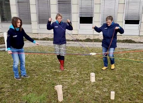 Foto: drei Frauen halten einen Holzklotz mit bunten Fäden in der Luft