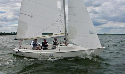Foto: Segelboot mit drei Männern auf dem Wasser