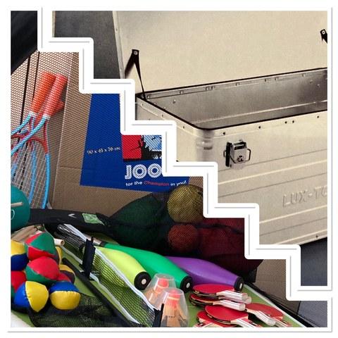 Foto: oben rechts Metallkiste, unten links Kleingeräte wie Jonglierbälle, Jonglierkeulen, Tischtenniskellen