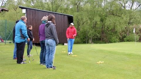 Foto: Gruppe von Personen auf grünem Rasen mit Golfschlägern