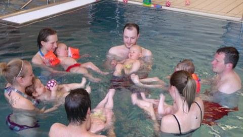Eltern mit Kleinstkindern im Schwimmbecken