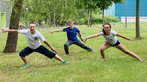 Foto: drei Personen in Taichi-Pose auf einer Wiese