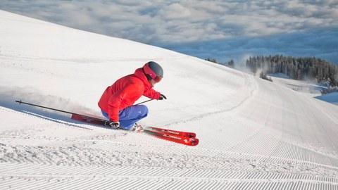 Foto Sportler mit roter Jacke fährt Abfahrtski