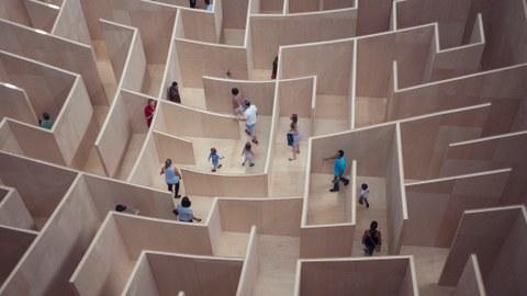 Ein Labyrinth aus Holz wird von mehreren Menschen durchschritten.