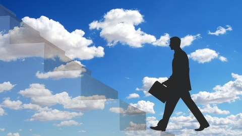 Mann mit Aktenkoffer geht eine Treppe hinauf. Im Hintergrund der Himmel