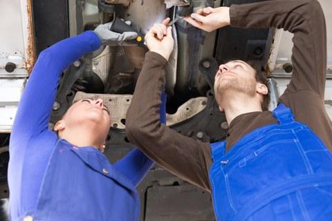 KfZ Mechatroniker reparieren Fahrzeug auf Hebebühne