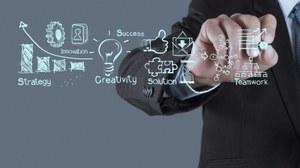 Mann zeichnet Business-Symbole auf eine Glasscheibe.