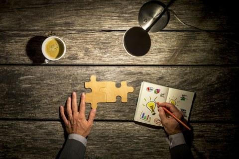 Holzschreibtisch mit Lampe, Kaffee, Puzzleteilen und einem Notizbuch
