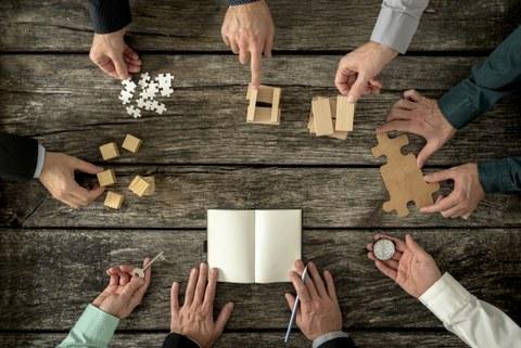 Mehrere Männer an einem Holztisch. Jeder hält etwas anderes in der Hand.